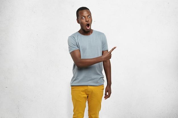 魅力的な面白いショックを受けた若い浅黒い肌の男性は、人差し指を灰色の空白の壁に横向きに向けて、驚くべき何かを示しています。人間の顔の表情と感情