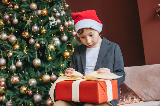 Attractive funny tween boy with dark hair in santa hat open gift box on christmas tree