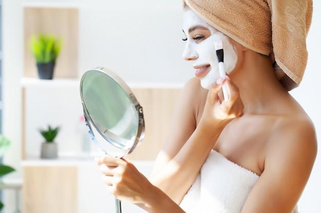 Привлекательная смешная женщина с глиняной маской на лице.