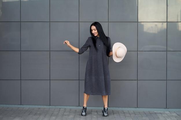 Привлекательная забавная молодая женщина, носящая молодое серое крупное платье и модную обувь, держащую стильную изящную шляпу модель в модном наряде позирует на городской серой стене открытый портрет.