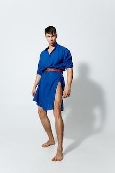 明るい背景のダンスの青いドレスを着た魅力的なゲイの男