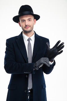 Attractive gentleman in black hat and coat putting on black leather gloves over white wall