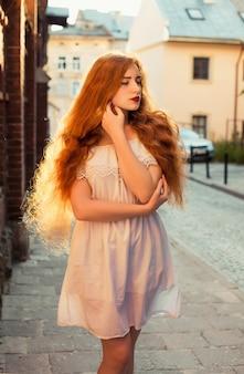 白い透明なドレスを着て長い髪の魅力的な生姜の女性