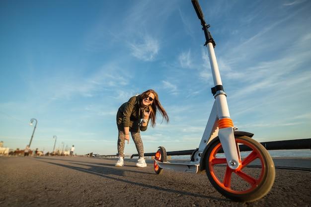 魅力的な女の子とアスファルト上の彼女のスクーター。笑顔と勝利のジェスチャーを示す若いひよこ。オレンジ色の車輪が付いている白いキックスクーター。本当の感情。