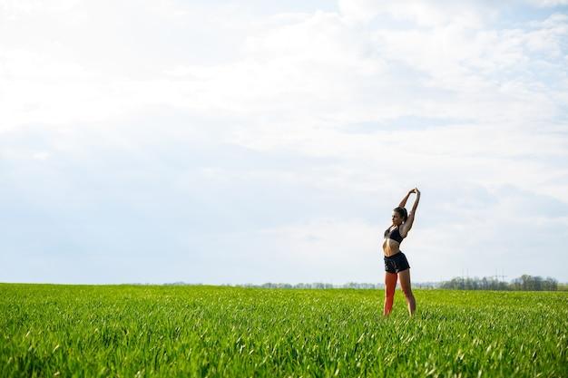 Привлекательная девушка-спортсменка делает разминку на открытом воздухе, упражнения для мышц. молодая женщина занимается спортом, здоровым образом жизни, спортивным телом. она в спортивной одежде, черном топе и шортах.