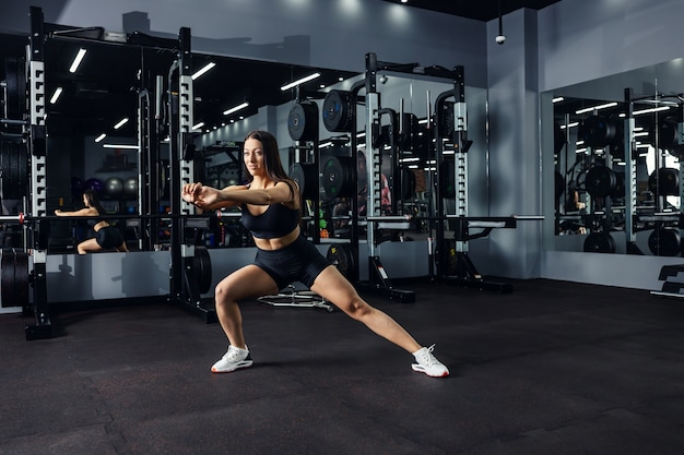 An attractive girl in black sportswear is doing functional calorie-burning lateral lunges in an indoor gym with a dark atmosphere