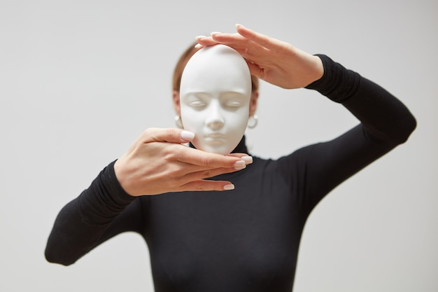 Attractive girl in a black sweater holds gypsum mask sculpture instead of face on a white wall, place for text. concept the masks we wear.