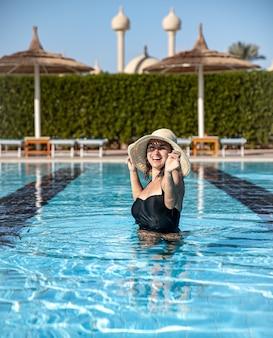 Attraente ragazza in costume da bagno nero e cappello bagna in piscina