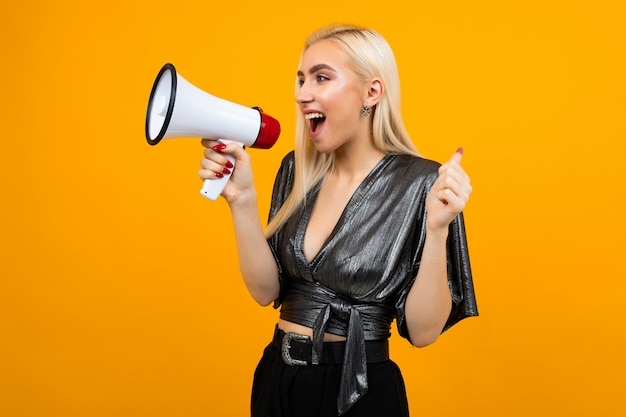 Attractive girl in a blouse shouting news in a megaphone on a yellow studio space