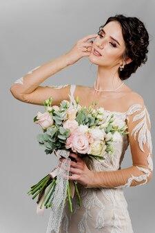 ウェディングブーケの魅力的な女の子の花嫁は微笑んで、左側を見て、彼女の顔に触れます。ソーシャルネットワークのための魅力的な女の子の縦の肖像画。