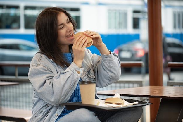 Una ragazza attraente in stile casual mangia un hamburger con un caffè seduto sulla terrazza estiva