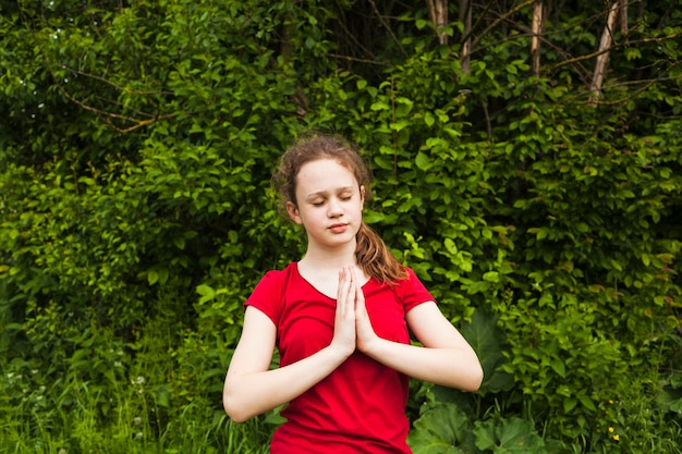 Attractive girl child praying with closed eyes in nature