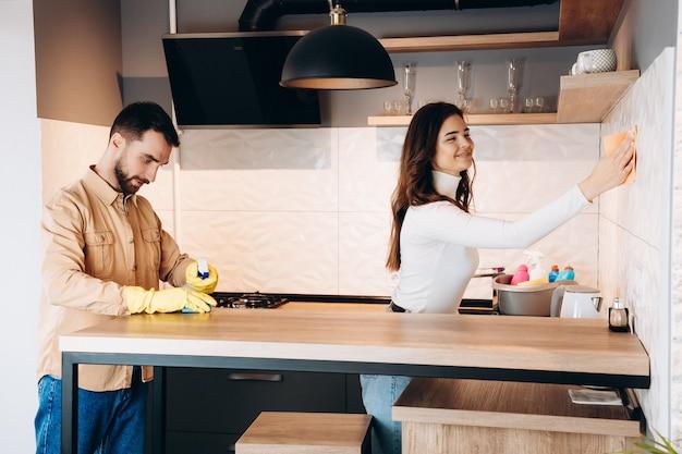 ゴム手袋で夫と一緒にキッチンを掃除する魅力的な女の子。きれいな家は幸せな家です。彼らのモダンなキッチンで拭くカジュアルな服を着た幸せなカップル。家の掃除。