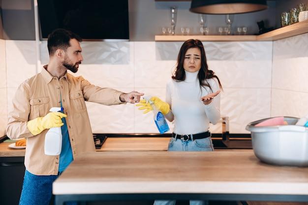 ゴム手袋をはめた夫と一緒に台所を掃除する魅力的な女の子が汚れているところを見せる