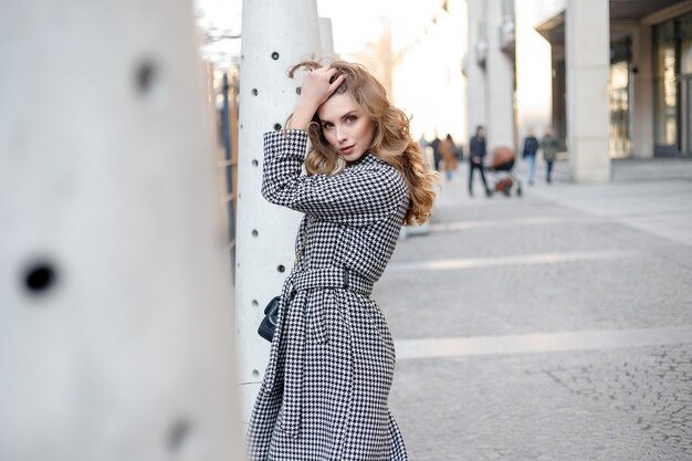 Attractive girl in a coat in the street in a city, sun is shining, than turns to camera and smiles. portrait happy slow motion summer face sunset beautiful lady outdoor closeup cute