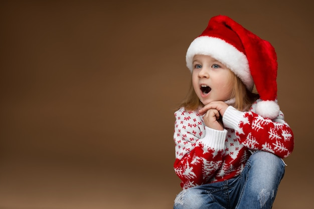 Attractive girl in cozy wear and christmas hat sits on the floor and sings a christmas song, picture isolated on brown background