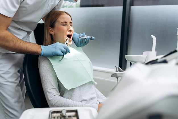 Attractive girl in a dental chair with closed eyes and open mouth. woman is afraid to treat teeth