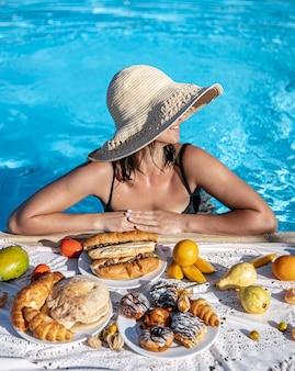 Ragazza attraente che gode di una deliziosa colazione nella piscina del resort