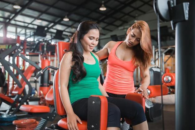 체육관에서 그녀의 허벅지를 운동하는 매력적인 여자
