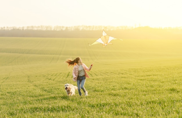 Attractive girl flying kite on field