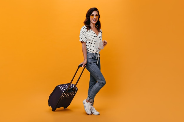 Attractive girl in glasses carries suitcase on orange background. brunette with wavy hair in sunglasses in white blouse with black polka dots posing.