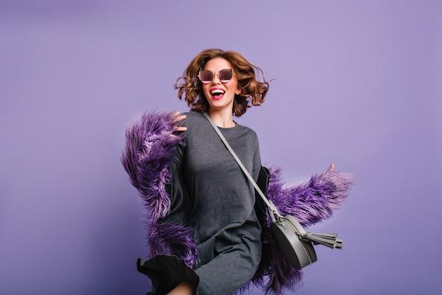Attraente ragazza in abito grigio e occhiali da sole neri ballando in studio su sfondo viola