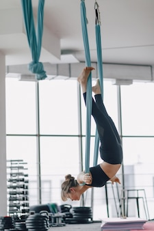 Attractive girl in the gym during yoga and fly yoga, posing and looking good