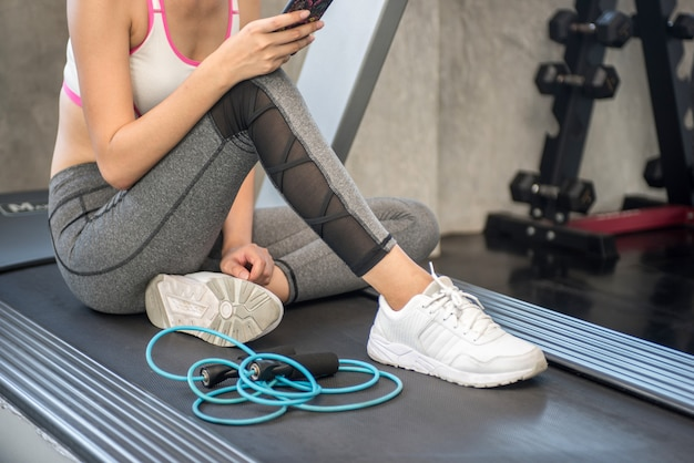 Attractive girl in the gym with a phone