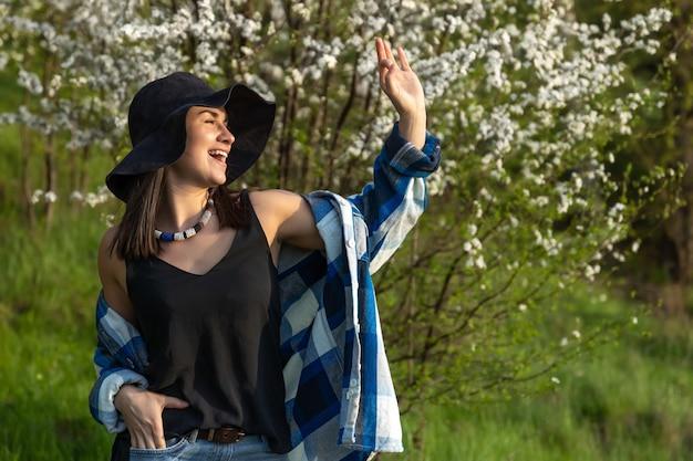 Ragazza attraente con un cappello tra gli alberi in fiore in primavera, in uno stile casual