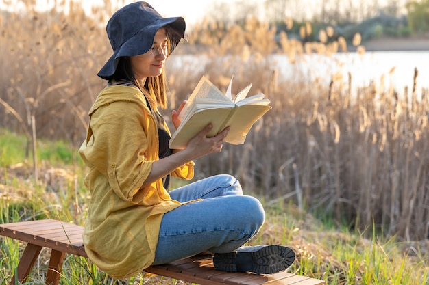 Attractive girl in a hat reads a book in nature at sunset.