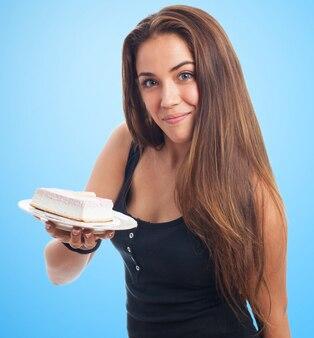 魅力的な女の子がケーキのクリーム状の部分を保持します。