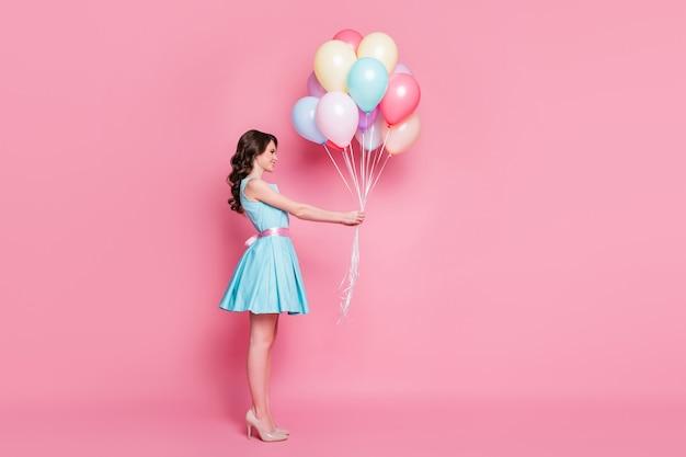 Привлекательная девушка держит в руке кучу гелиевых шаров, изолированных на розовом фоне пастельных тонов