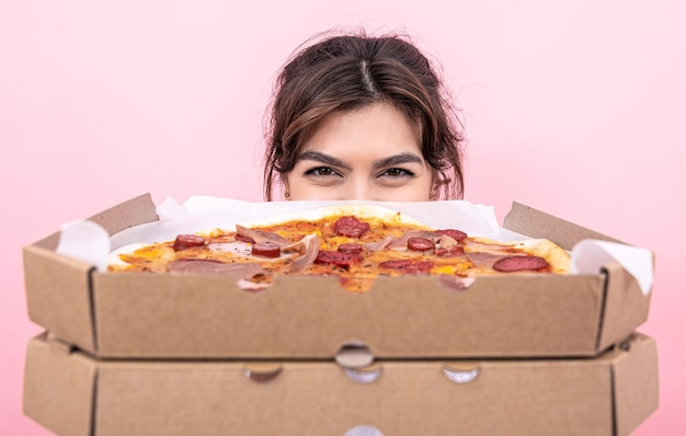 Attractive girl holding pizza in a cardboard box on a pink background