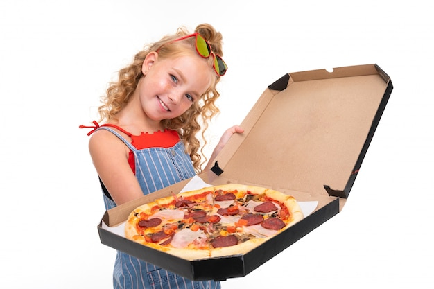 Attractive girl holds an open box with pizza on white wall