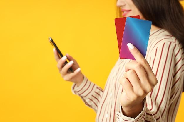 魅力的な女の子は黄色の背景に電話とクレジットカードを保持しています。
