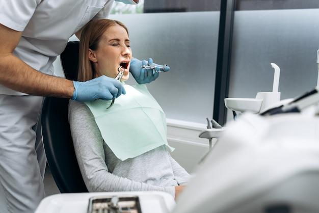目を閉じて口を開けた歯科用椅子の魅力的な女の子。女性は歯を治療することを恐れています
