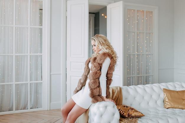 Привлекательная девушка в шубе и свитере позирует у дивана и елки в яркой гостиной дома