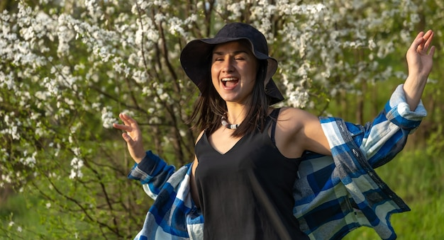 캐주얼 스타일에 봄에 꽃 피는 나무 사이 모자에 매력적인 여자.