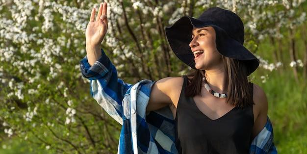 カジュアルなスタイルで、春の花の木の中で帽子をかぶった魅力的な女の子