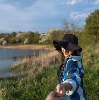湖のほとりの散歩に日没時に帽子をかぶった魅力的な女の子