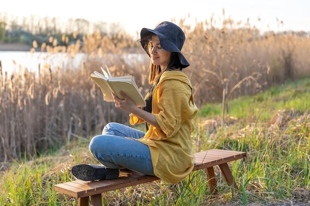 모자에 매력적인 여자 일몰 자연 속에서 책을 읽습니다.