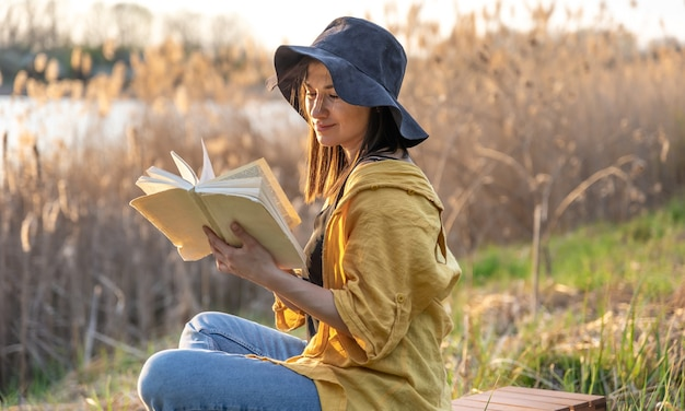 帽子をかぶった魅力的な女の子が日没時に自然の中で本を読む