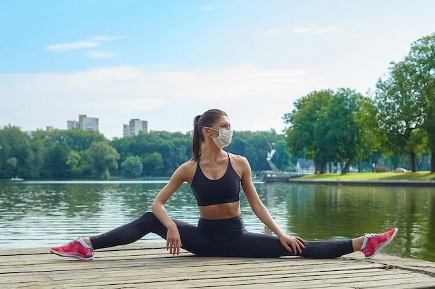 Привлекательная девушка в маске и спортивной одежде делает гимнастические упражнения на деревянном пирсе в городском парке. концепция безопасной тренировки на открытом воздухе