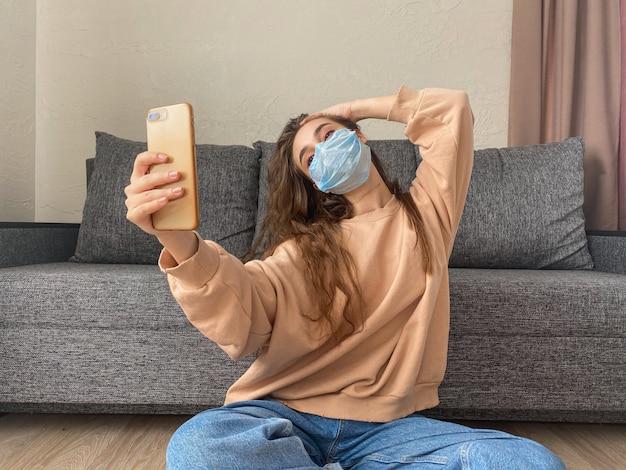 医療マスクの魅力的な女の子は、コロナウイルスのパンデミックによる自宅での自己分離で座っているスマートフォンで自分撮りを取る