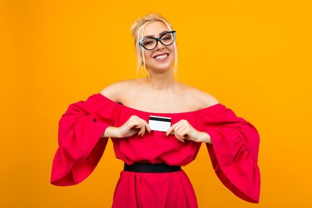 Привлекательная девушка в красном платье держит кредитную карту с макетом для банка на желтом пространстве