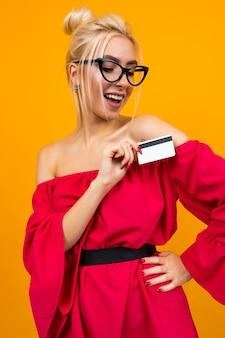 Привлекательная девушка в красном платье держит кредитную карту с макетом для банка на желтом