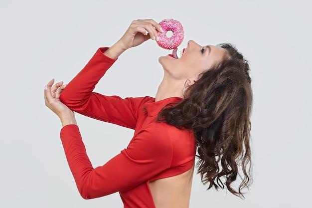 Привлекательная девушка в красном платье лижет пончик
