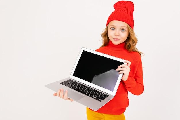 Привлекательная девушка в красной шляпе показывает экран ноутбука