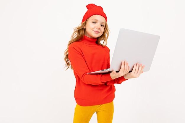 Привлекательная девушка в красной шляпе пишет сообщение на ноутбуке на белом фоне студии