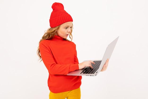 Привлекательная девушка в красной шляпе пишет сообщение на ноутбуке